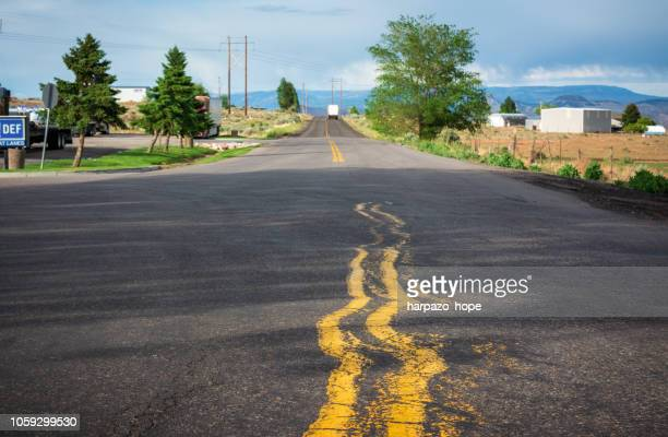 squiggly double yellow lines in the road. - fracasso imagens e fotografias de stock
