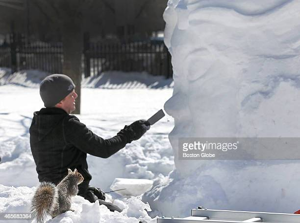 A squirrel acts as art critic while artist Sean Fitzpatrick from Saugus Mass makes a sculpture as a part of the commission he received from Boston...