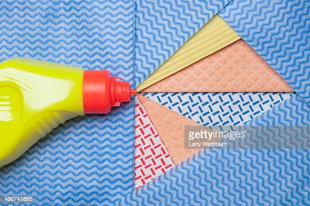 Squirt of a household cleaner represented by segmented cut-outs of dishcloths