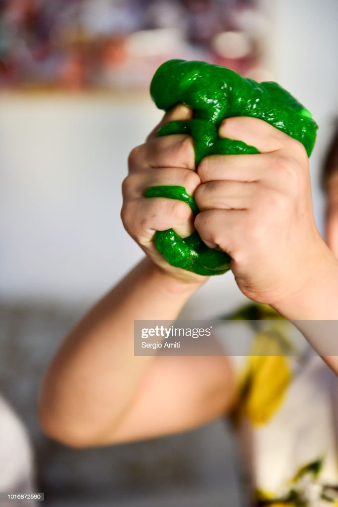 Squishing a piece of green slime : Stock Photo