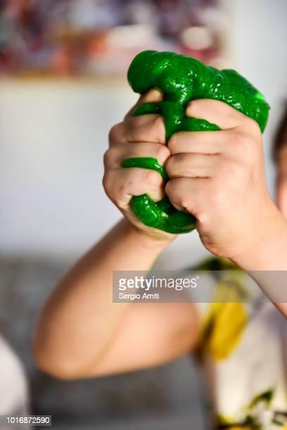 squishing a piece of green slime - foam finger - fotografias e filmes do acervo
