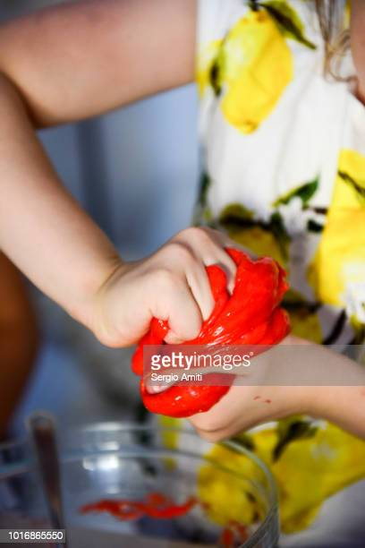 squishing a piece of red slime - thick girls stock photos and pictures
