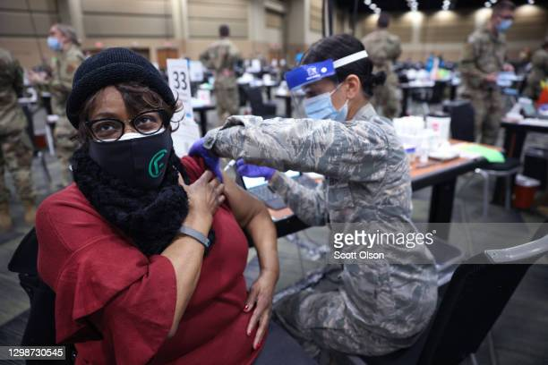 SrA Serena Nicholas of the Illinois Air National Guard administers a COVID-19 vaccine to Larcetta Linear at a mass vaccination center established at...