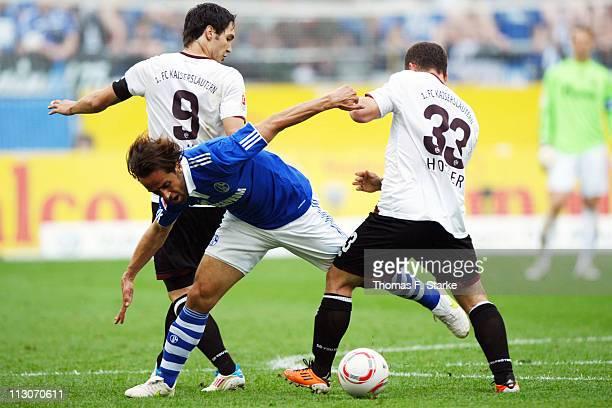 Srdjan Lakic and Erwin Hoffer of Kaiserslautern tackle Ali Karimi of Schalke during the Bundesliga match between FC Schalke 04 and 1 FC...