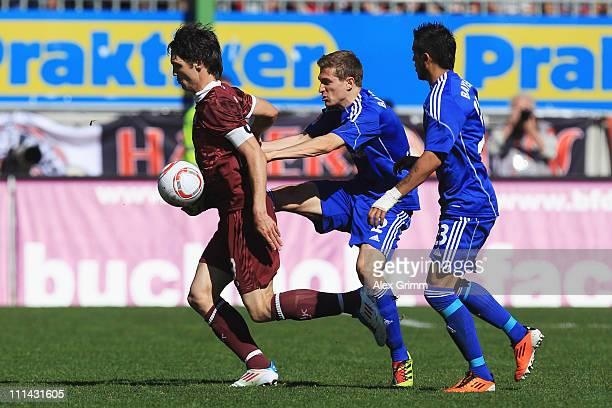 Srdjan Lakic of Kaiserslautern is challenged by Daniel Schwaab and Arturo Vidal of Leverkusen during the Bundesliga match between 1. FC...