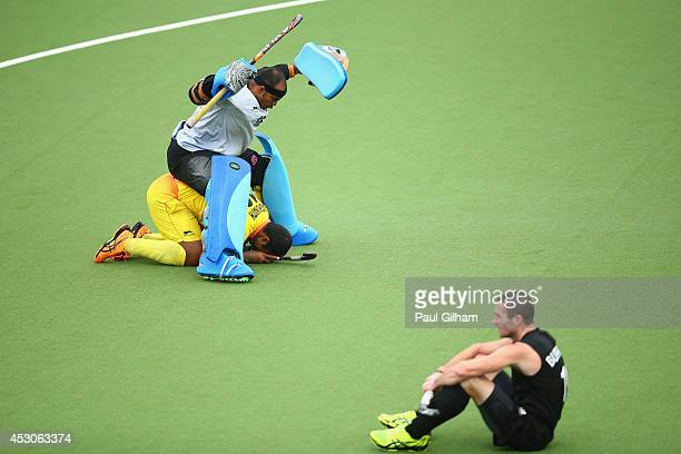 Sreejesh Parattu Raveendran and Raghunath Ramachandra of India celebrate winning as Phil Burrows of New Zealand looks dejected in the Men's SemiFinal...