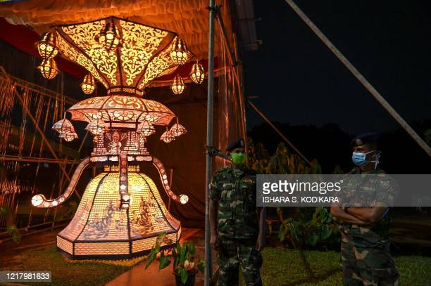 Sri Lanka Army officers stand guard near lanterns displayed near the military headquarters in the capital Colombo on June 6 a day after the Poson...