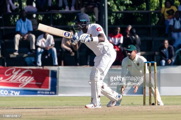 Sri Lanka batsman Angelo Mathews is in action as slip fielder Craig Ervine looks on during the third day of the first Test cricket match played...