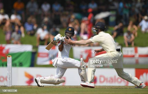Sri Lanka batsman Dimuth Karunaratne hits out past Keaton Jennings during Day Two of the Second Test match between Sri Lanka and England at Pallekele...