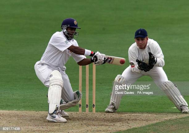Sri Lanka batsman Hashan Tillakaratne square cuts a delivery from Glamorgan's Robert Croft as wicketkeeper Mark Wallace looks on during the first...