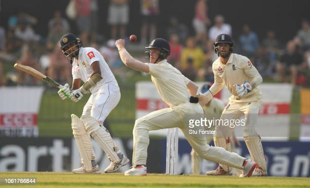 Sri Lanka batsman Suranga Lakmal hits past Keaton Jennings as Ben Foakes looks on during Day Two of the Second Test match between Sri Lanka and...