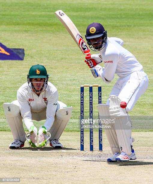 Sri Lanka batsman Upul Tharanga is in action as wicket keeper Peter Moor looks on during the second day's play in the first Test match between Sri...