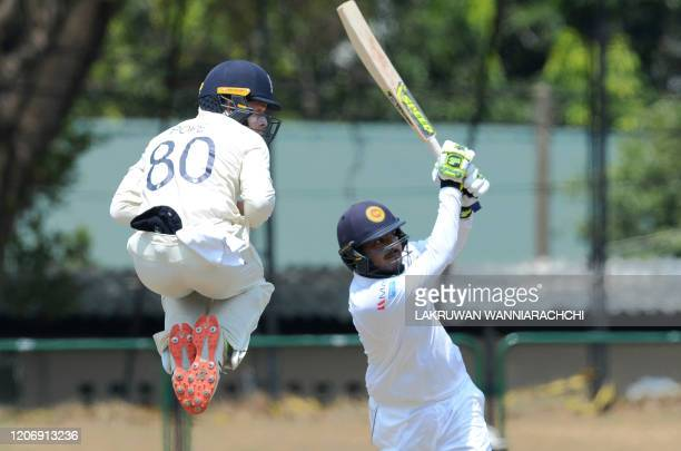 Sri Lanka Board President's XI Angelo Perera plays a shot as England's Ollie Pope jumps during the second day of a four-day practice match between...