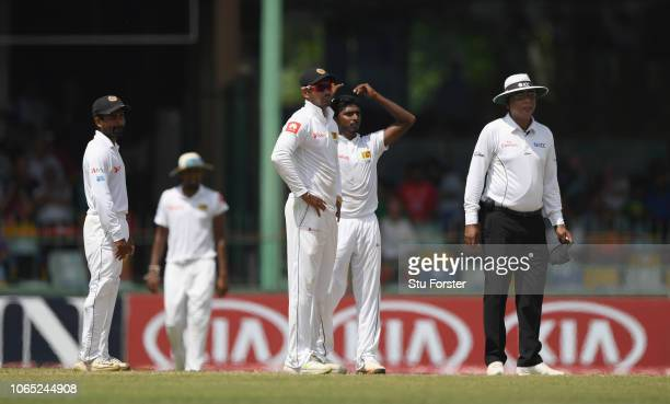 Sri Lanka bowler Lakshan Sandakan reacts after he takes a wicket for the second time in the innings with a no ball as umpire Sundaram Ravi watches...