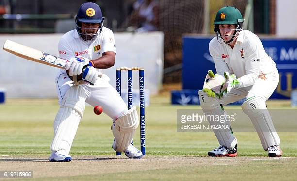 Sri Lanka captain Rangana Herath is in action as wicketkeeper Peter Moor looks on during the second day's play in the first Test match between Sri...