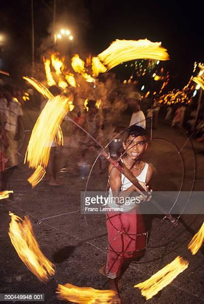 Sri Lanka, Colombo, boy spinning fire wheel at Perahera festival