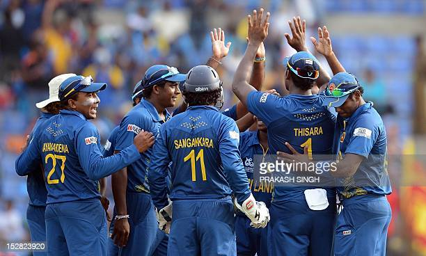 Sri Lanka cricket captain Mahela Jayawardene celebrates the wicket of New Zealand cricketer Martin Guptill with bowler Akila Dananjaya and teammates...