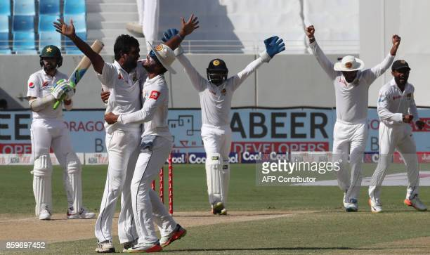 Sri Lanka cricket players celebrate the dismissal of Muhammad Amir of Pakistan during the Test cricket match between Pakistan and Sri Lanka at Dubai...