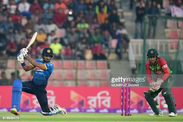 Sri Lanka cricketer Danushka Gunathilaka plays a shot as the Bangladesh wicketkeeper Mushfiqur Rahim looks on during the second Twenty20 cricket...