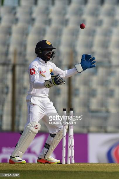 Sri Lanka cricketer Niroshan Dickwella celebrtes after the dismissal of the Bangladesh cricketer Tamim Iqbal during the first day of the first...