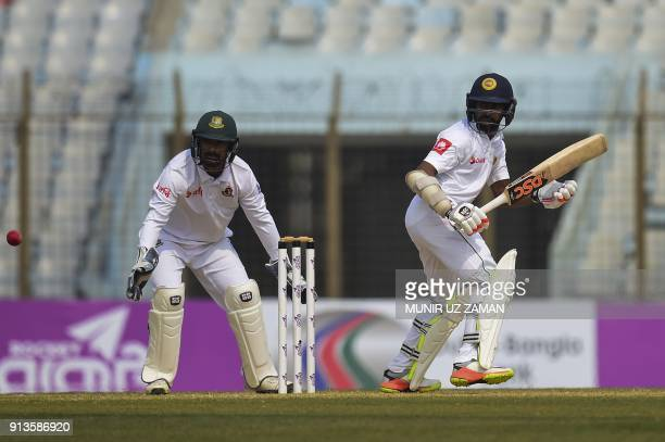 Sri Lanka cricketer Niroshan Dickwella plays a shot as the Bangladesh wicketkeeper Liton Das looks on during the fourth day of the first cricket Test...