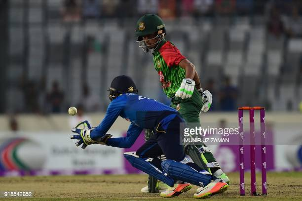 Sri Lanka cricketer Niroshan Dickwella takes a catch successfully to dismiss Bangladesh cricketer Afif Hossain during the first Twenty20 cricket...