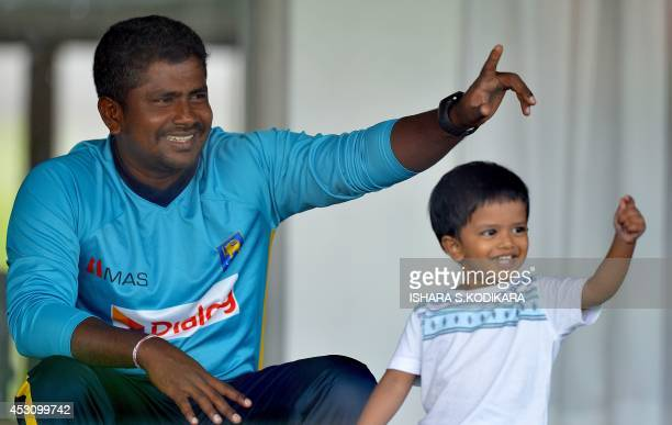 Sri Lanka cricketer Rangana Herath and his son gesture during a practice session at the Galle International Cricket Stadium in Galle on August 3 2014...