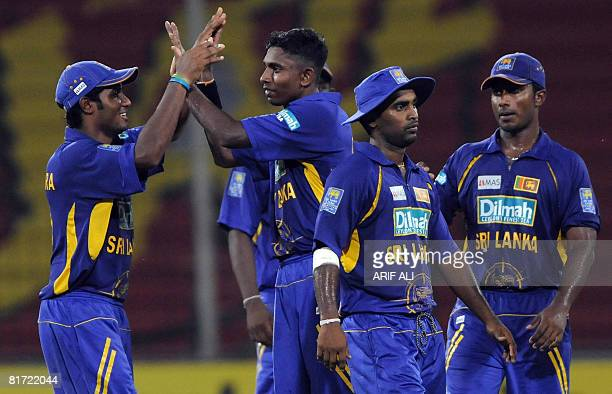 Sri Lanka cricketer Thilina Thushara Mirando celebrates the wicket of UAE's Indika Batuwitaarachchi with teammates during a Group A match between Sri...