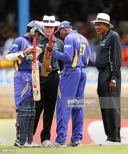 Sri Lanka cricketer Upul Tharanga changes his bat brought by Thilan Thusharaf Mirando as umpires Simon Taufel and Clyde Dunmcan look on during the...