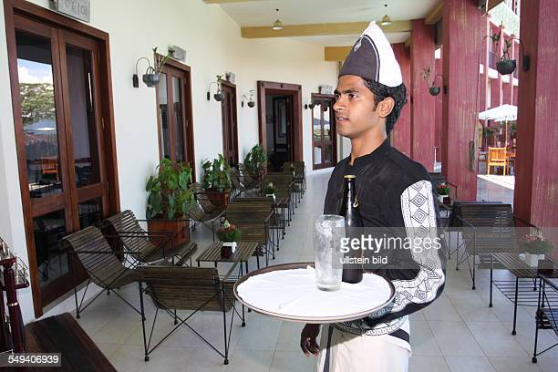 Pupil of the Don Bosco center for vocational training for former street kids or children of poor families A waiter with a cap