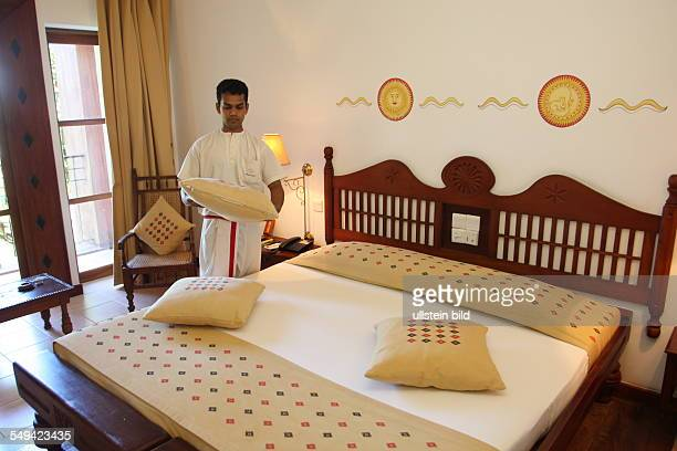 Pupils of the Don Bosco center for vocational training for former street kids or children of poor families A young man makes the bed of a hotel room