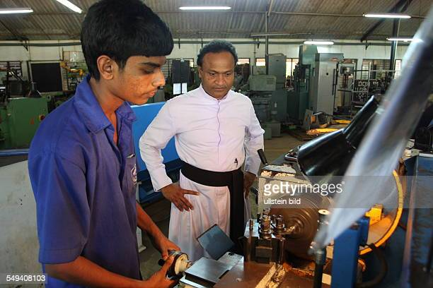 Father Shiran leader of the Don Bosco technical center and a trainee working on a maschine
