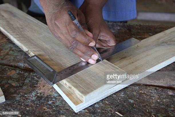 The Salesian fight against pedophilia and helps the young boys to get education A trainee measures a piece of wood
