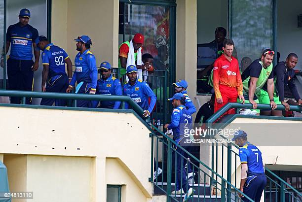 Sri Lanka players return to their changing rooms after rain delayed the fourth trination One Day International cricket match between Zimbabwe and...
