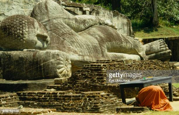 Sri Lanka Polonnaruwa Buddhist monk praying in front of giant reclining Buddha figure