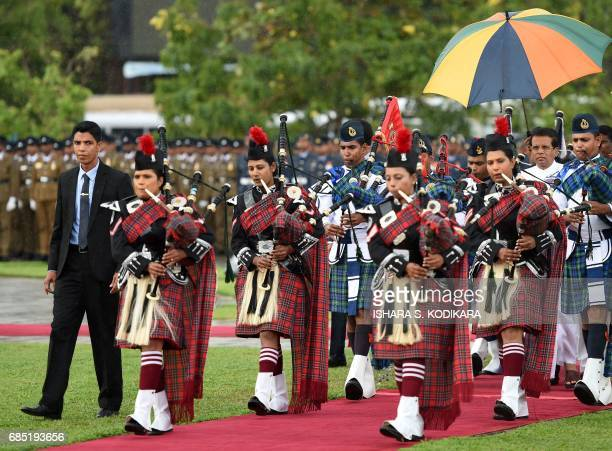 Sri Lanka President Maithripala Sirisena arrives with a bagpipe band during a commemorative ceremony in Colombo on May 19 2017 marking the eight...