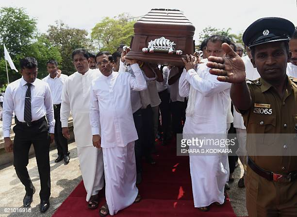 Sri Lanka President Maithripala Sirisena assists in carrying the coffin of legendary musician W D Amaradeva during his funeral at Independence Square...