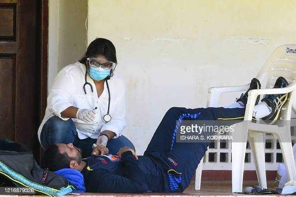 Sri Lanka skipper Dimuth Karunaratne receives medical attention after suffering what he called a heat stroke on the first day of their outdoor...