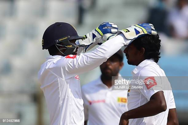 Sri Lanka wicketkeeper Niroshan Dickwella congratulates his teammate Lakshan Sandakan after the dismissal of the Bangladesh cricketer Imrul Kayes...