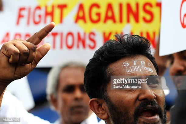 Sri Lankan activist from Frontline Socialist Party shouts a slogan as others hold placards during a demonstration in Colombo on December 10 demanding...