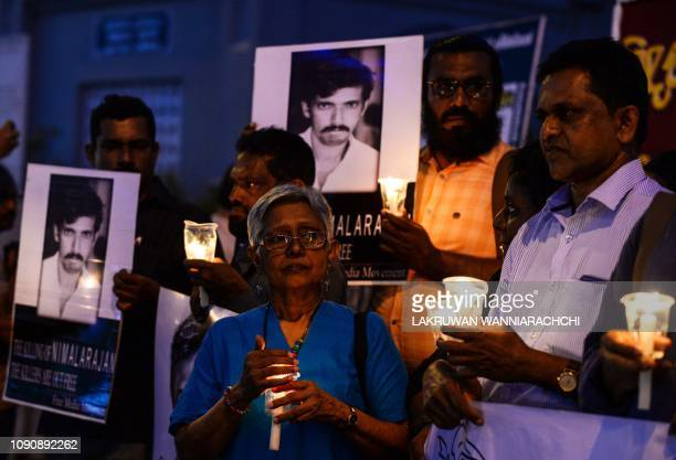 Sri Lankan activists from the Free Media Movement hold candles and placards during a vigil organized to pay tribute to colleagues being killed in...