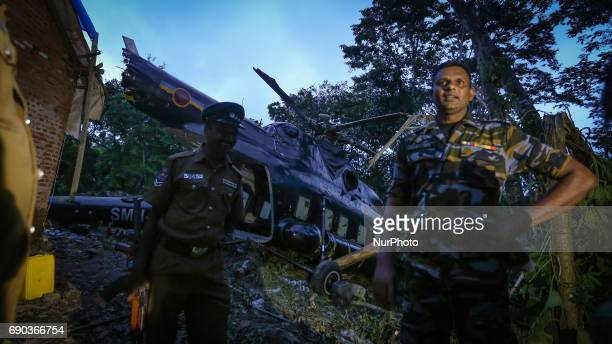 A Sri Lankan Air Force officer looks on infront of the crashlanded MI17 helicopter that was carrying relief aid to flood victims in a flooded village...