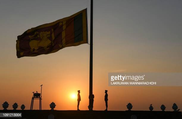 Sri Lankan Air force officers stand while the national flag is lowered as part of a daily ceremony during sunset at the Galle Face Green promenade in...