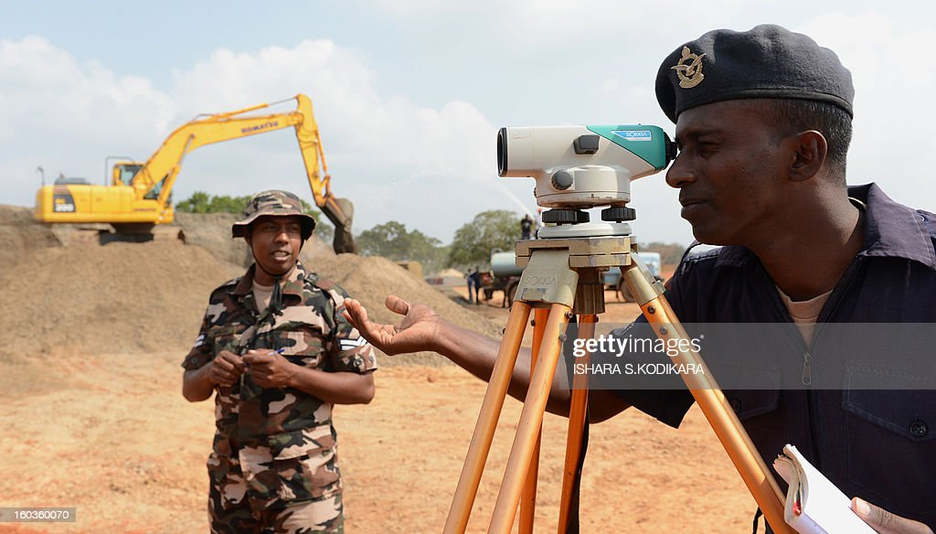 Sri Lankan air force personnel work on a new runway in northern region of Kilinochchi on January 30, 2013, the former stronghold of Tamil Tiger rebels who were defeated by security forces in May 2009. Troops captured the Iranamadu air strip from the rebels during the war and now the facility is being developed as a domestic airport. AFP PHOTO/ Ishara S