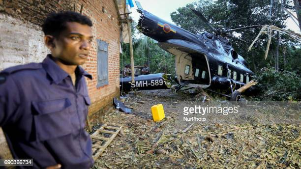 A Sri Lankan Air Force soldier looks on beside the crashlanded MI17 helicopter that was carrying relief aid to flood victims in a flooded village...