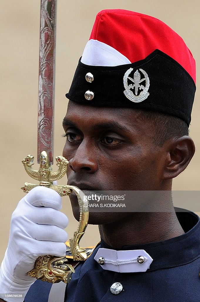 A Sri Lankan army cadet holds up a ceremonial sword during a