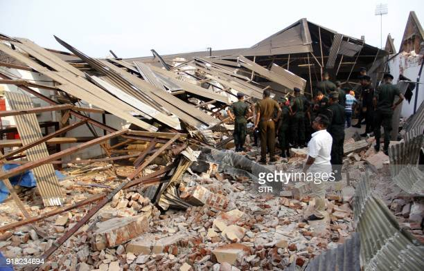 Sri Lankan Army officers remove rubble at the site of a collapsed storehouse in Colombo on February 14 2018 The roof of a tea storage facility...