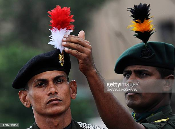 A Sri Lankan Army official adjusts the cap of a soldier before a ceremony at the Army headquarters in Colombo on June 17 2013 Sri Lankas outgoing...