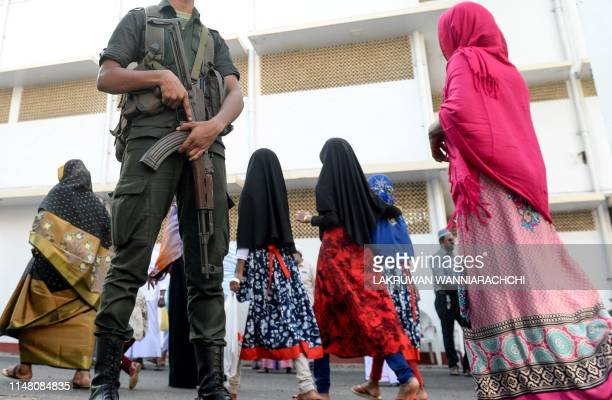 Sri Lankan Army personnel stand guard as Muslim devotees arrive to offer prayers on the first day of Eid alFitr at the Grand Mosque in Colombo on...
