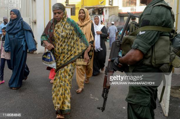 TOPSHOT Sri Lankan Army personnel stand guard as Muslim devotees arrive to offer prayers on the first day of Eid alFitr at the Grand Mosque in...